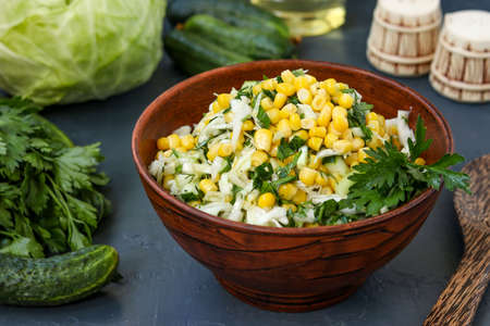 Healthy salad with cabbage, cucumbers, corn and parsley in a salad bowl on a dark background, horizontal photo, close-up Banco de Imagens