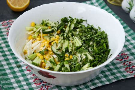 Cooking healthy salad with cabbage, cucumbers, corn and parsley, mixing vegetables in a salad bowl, horizontal photo, close-up