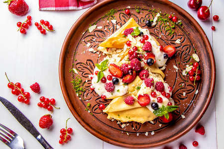 Homemade pancakes with sour cream and berries on a white background close-up, horizontal photo, top view