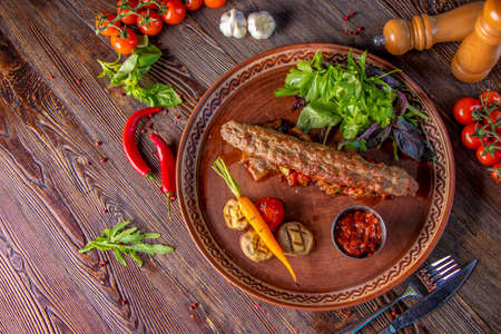 Turkish and Arabic Traditional Ramadan mix kebab plate, Kebab lamb and beef with baked vegetables, mushrooms and tomato sauce. Top view, close-up, horizontal photo