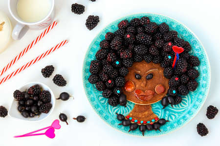 Baby girl face made of pancakes, gooseberries and blackberries, culinary art Banco de Imagens