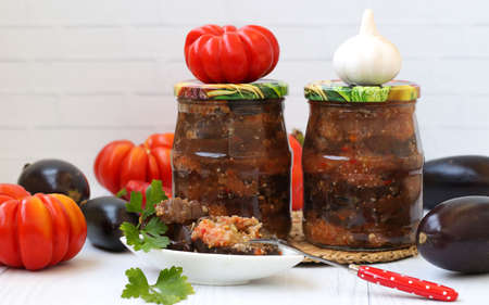 Eggplants in acute sauce of pepper, tomatoes and garlic in jar on the table, close-up, horizontal orientation, Harvesting vegetables for the winter Stock Photo