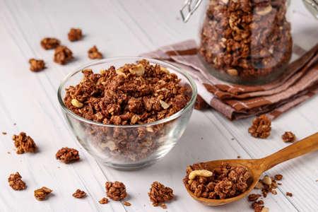 Muesli croustillant de granola avec du miel naturel, du chocolat et des noix dans un bol en verre sur fond blanc, nourriture saine, gros plan, orientation horizontale
