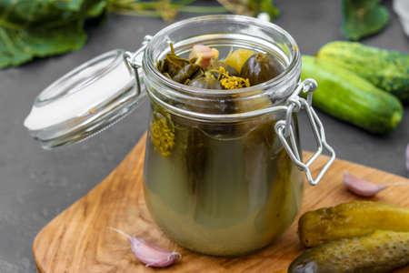 Sottaceti - cetrioli fermentati in scatola in barattolo di vetro su sfondo scuro, orientamento orizzontale, primo piano