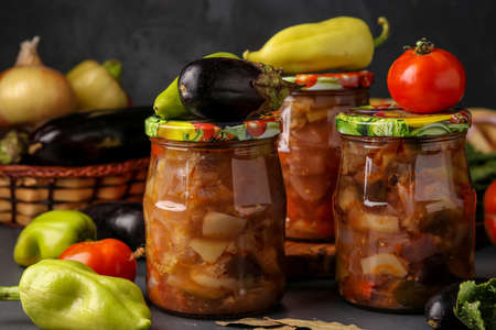 Vegetable salad with eggplant, onions, peppers and tomatoes in jars on a dark background, horizontal orientation, close up