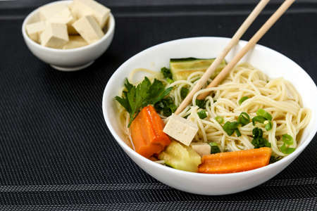 Traditional asian soup with tofu cheese, noodles, carrots and zucchini on dark background. This dish usually contains bouillon and vegetables, close up Zdjęcie Seryjne