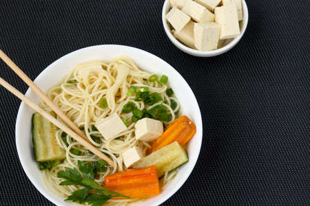 Traditional asian soup with tofu cheese, noodles, carrots and zucchini on dark background. This dish usually contains bouillon and vegetables, top view, close up