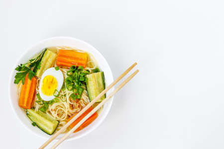 Traditional asian soup with noodles, carrots, zucchini and boiled egg on white background, dish usually contains bouillon and vegetables, top view, copy space