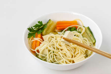Traditional asian soup with tofu cheese, noodles, carrots and zucchini on white background. This dish usually contains bouillon and vegetables, close up