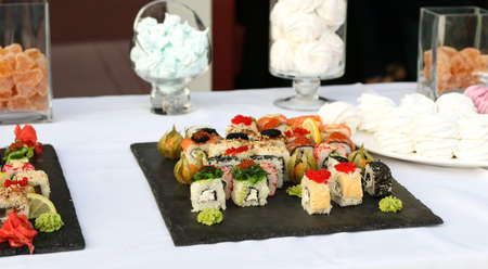 Set of sushi rolls with vasabi and ginger on a dark slate plate, Buffet table, horizontal orientation, sweets in the background