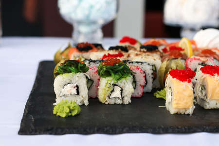 Set of sushi rolls with vasabi and ginger on a dark slate plate, Buffet table, horizontal orientation, close up