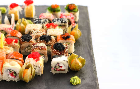 Set of sushi rolls with vasabi and ginger on a dark slate plate, Buffet table, horizontal orientation, close up, copy space Zdjęcie Seryjne