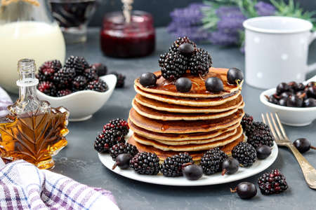 Pancakes with maple syrup, blackberries and currants are stacked on a plate, in the background berries and a jug of milk, closeup, horizontal orientation