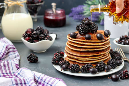 Homemade pancakes with blackberries and currants are stacked on a plate and watered with maple syrup, in the background berries and a jug of milk, closeup, horizontal orientation