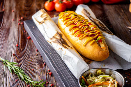 Hot dog with sausage is located on a wooden board against a dark background, rustic style, horizontal orientation