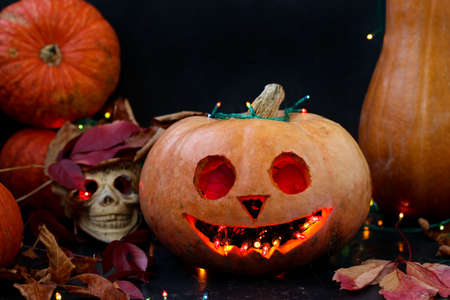 Halloween Creative composition with a skull and a Scary pumpkin on dark background, close up, horizontal orientation