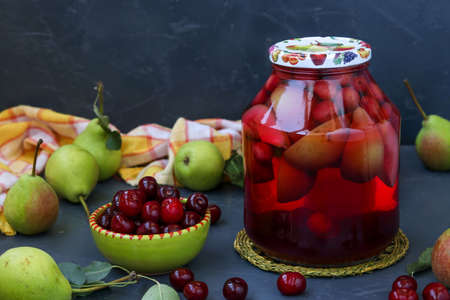 Compote of pears and cherries in jar on dark background, harvest for the winter, horizontal orientation, copy space, close-up