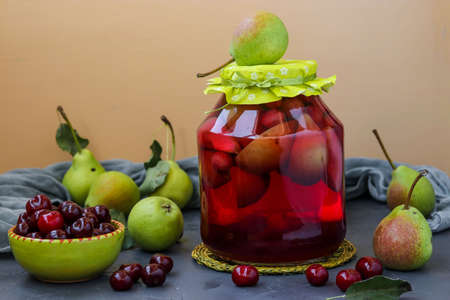 Compote of pears and cherries in jar on table, harvest for the winter, horizontal orientation, close-up