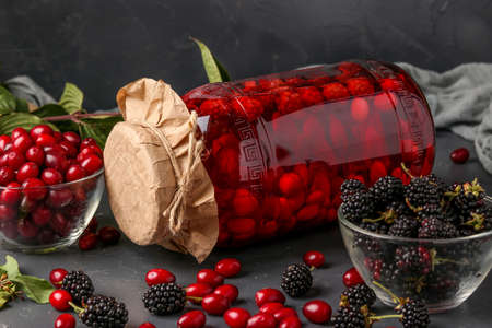 Dogwood compote with blackberry in jar on a dark background, horizontal orientation, close-up