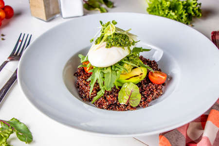 Quinoa with avocado, poached egg and microgreen in a white plate, horizontal orientation, close-up, top view