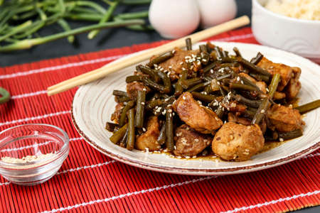 Fried pork with garlic arrows and soy sauce, sprinkled with sesame seeds in a plate, on a red mat, horizontal orientation, closeup Banque d'images