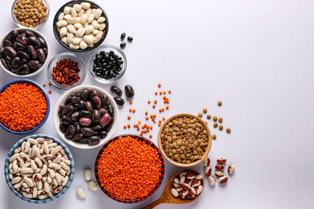 Red and brown lentils, black, brown and white beans are legumes that contain a lot of protein are located in bowls on white background, concept is healthy eating, top view, copy space, horizontal orientation