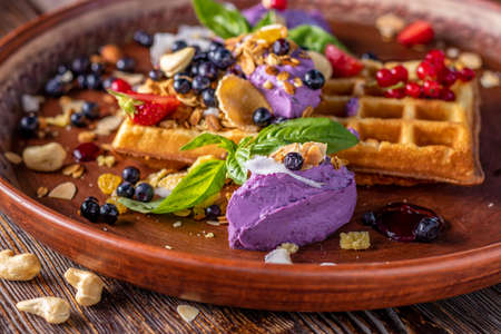 Belgian waffles with blueberry cream, granola and fresh berries, Tasty breakfast, Horizontal orientation, Closeup