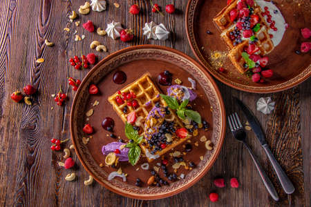 Varieties of Belgian waffles with blueberry cream and cheese cream, granola, nuts and fresh berries, rustic style, Tasty breakfast, Horizontal orientation, Top view, Closeup