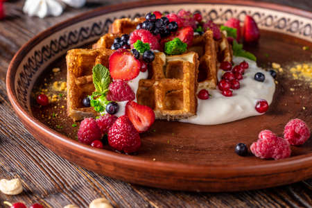 Belgian waffles with berries, nuts and cream cheese in a plate on a wooden table, Tasty breakfast, Horizontal orientation, Closeup