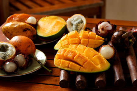 Tropical fruits: passion fruit, rambutan, mangosteen and mangoes are located on a wooden table 写真素材