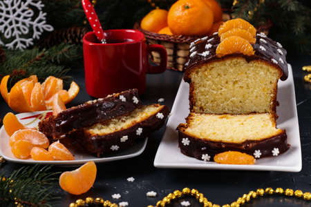 Cupcake with tangerines, covered with chocolate glaze is located on the New Year's background, Horizontal orientation, close-up