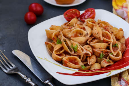 Conchiglie Italian pasta shells with cherry tomatoes and tomato sauce on dark background, horizontal orientation, closeup