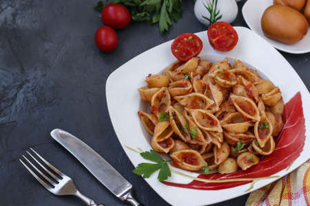 Conchiglie Italian pasta shells with cherry tomatoes and tomato sauce on dark background, horizontal orientation, top view, copy space Stok Fotoğraf