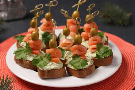 Snack on a festive table - canapes with salmon, cream cheese, olives and avocado Stock Photo