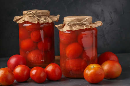 Homemade salted tomatoes in jars on a dark background, Fermented food, closeup, copy space Stok Fotoğraf