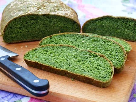 Homemade bread with nettles green, cut into slices and is located on a wooden board, horizontal orientation