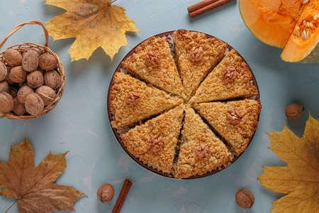 Homemade pumpkin pie with walnuts, sliced, on a light blue background, Top view, Closeup, horizontal orientation