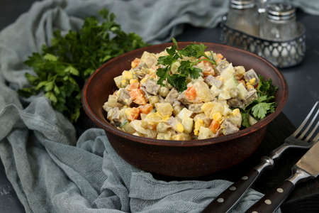 Traditional Russian festive salad Olivier with tongue in a bowl against a dark background, Closeup, horizontal orientation Reklamní fotografie