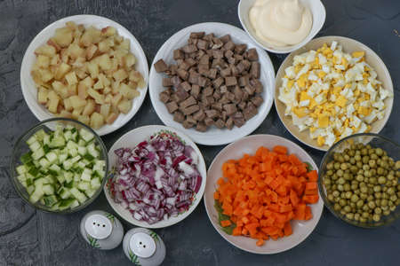 Ingredients for the preparation of Olivier salad: beef tongue, cucumbers, red onions, potatoes, carrots, eggs, canned peas and mayonnaise, top view on a dark background