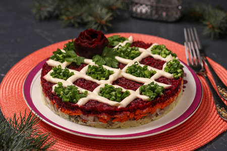 Traditional Russian holiday salad Herring under a fur coat on a Christmas background, Closeup, horizontal orientation