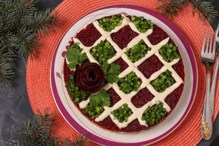 Traditional Russian holiday salad Herring under a fur coat on a Christmas background, Closeup, Top view, horizontal orientation