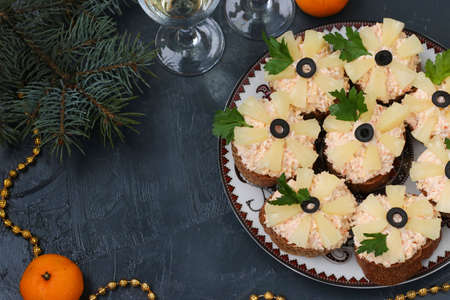 Canapes with cream cheese, crab sticks, black olives and pineapples on dark background, horizontal orientation
