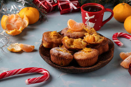 Homemade muffins with tangerines, sprinkled with powdered sugar is located on the New Year's or Christmas light blue background, Closeup