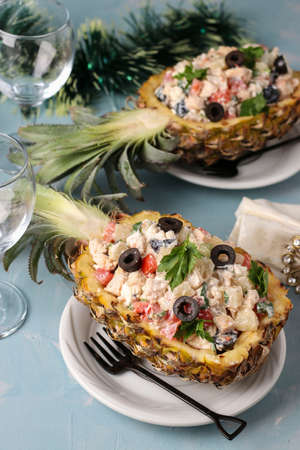 Festive salad with chicken in halves of pineapple on a light blue background, New Year, Valentines Day, Romantic dinner, Closeup, vertical orientation