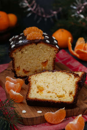 Cupcake with tangerines, covered with chocolate glaze is located on the New Year's background, Vertical orientation, Festive still life
