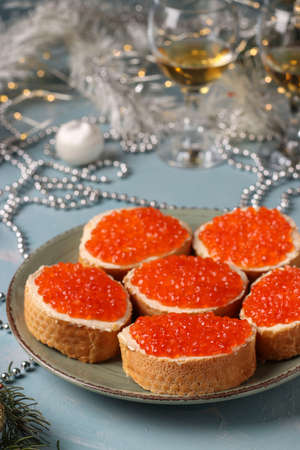 Sandwiches with red caviar are located on a plate against a light blue background, Festive snack, Closeup, vertical orientation Stock fotó