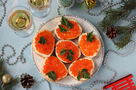 Sandwiches with red caviar are located on a plate against a light blue background, Festive snack, horizontal orientation, Top view Stock fotó