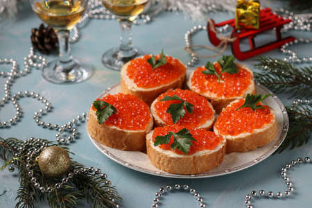 Sandwiches with red caviar are located on a plate against a light blue background, Festive snack, horizontal orientation, Closeup