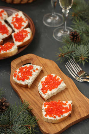 Sandwiches with red caviar are located on a wooden board against a dark background, Festive snack, Closeup