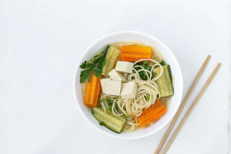 Traditional asian soup with tofu cheese, noodles, carrots and zucchini on white background, dish usually contains bouillon and vegetables, Horizontal orientation, Top view